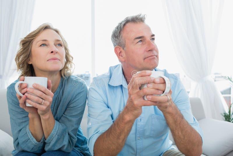 O meio pensativo envelheceu os pares que sentam-se no sofá que come o café imagem de stock