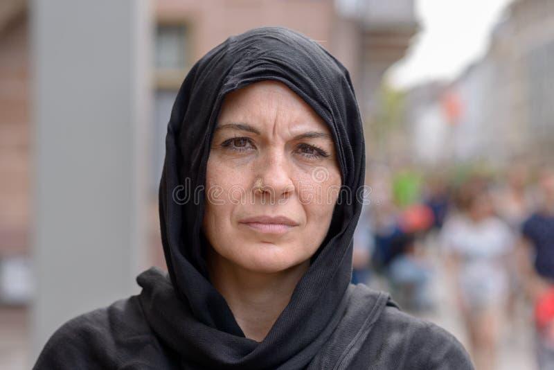 O meio sério envelheceu a mulher que veste um lenço principal imagem de stock