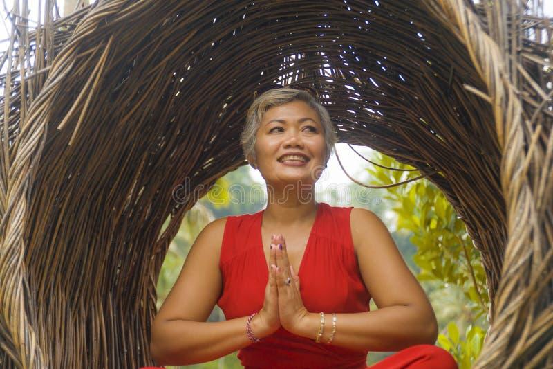 O meio 40s ou 50s atrativo e feliz envelheceu a mulher asiática no abrandamento praticando da ioga do vestido vermelho elegante e imagem de stock