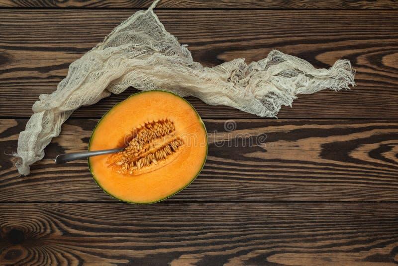 O melão orgânico do cantalupo corta a situação na placa de corte de madeira w fotografia de stock