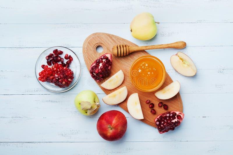 O mel, as fatias da maçã e a romã servem na opinião superior da placa da cozinha A tabela ajustou-se com alimento tradicional par foto de stock royalty free