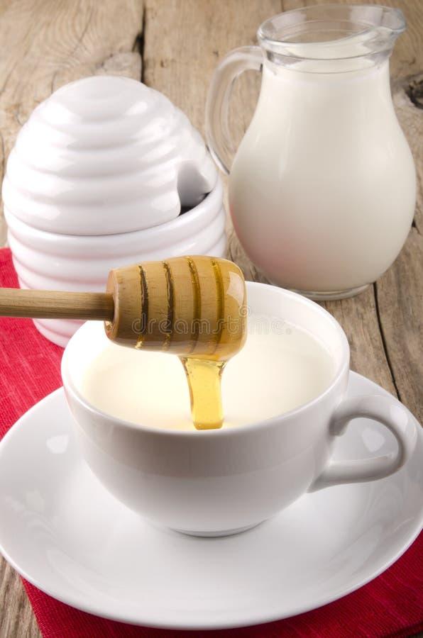 O mel flui em um copo com leite morno fotos de stock royalty free