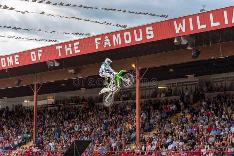 O membro da equipa do motocross do estilo livre lança-se fora da rampa no ar durante o desempenho foto de stock royalty free