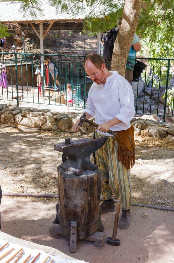 O membro do festival anual dos cavaleiros do Jerusalém, vestidos como um ferreiro forja o detalhe do ferro imagens de stock