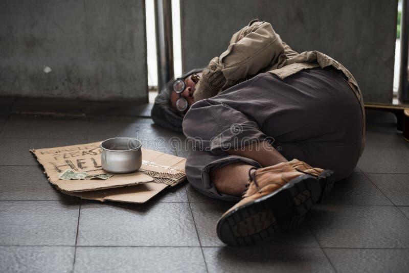 O mendigo doente idoso ou o sono sujo desabrigado do homem no passeio com doam a bacia, nota de dólar, moeda, cartão do papel com fotografia de stock
