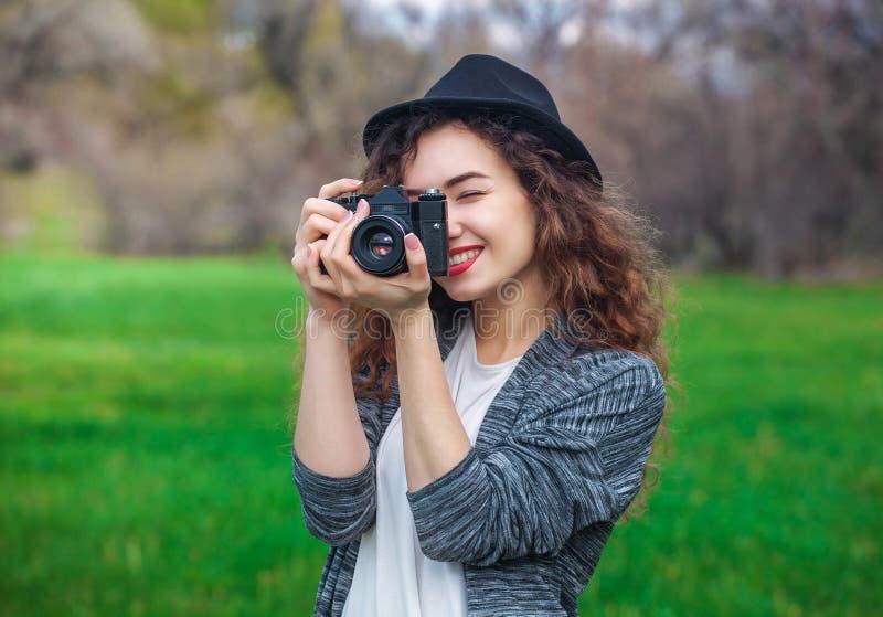 O menina-fotógrafo bonito com o cabelo encaracolado que guarda uma câmera velha e toma uma imagem foto de stock
