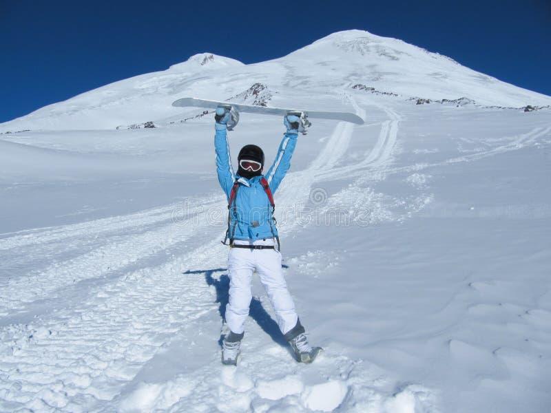 O menina-snowboarder está na frente das partes superiores da montanha que guardam um snowboard sobre sua cabeça em um dia ensolar foto de stock royalty free