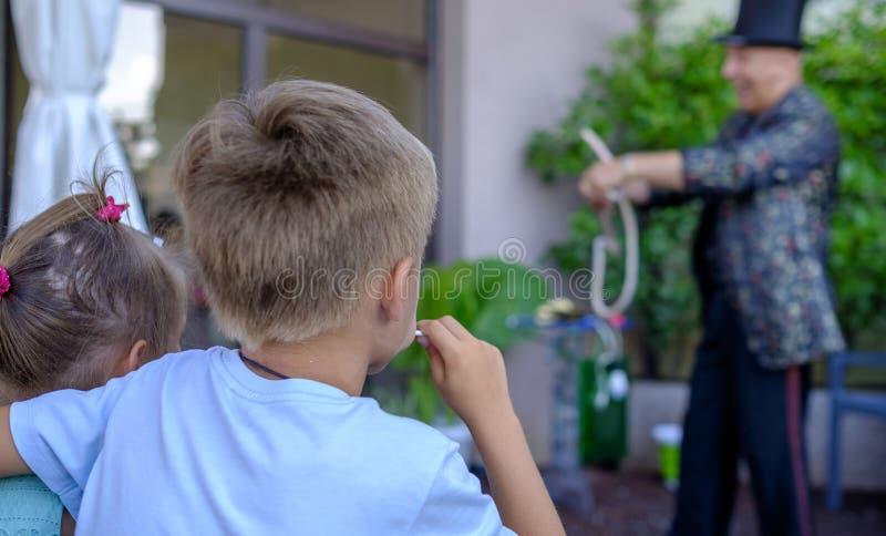 O menino é de assento e de observação a mostra dos mágicos foto de stock royalty free