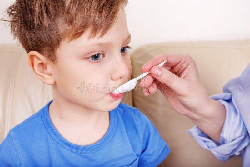 O menino é doente A mamã trata drogas fotos de stock