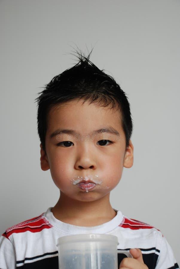 O menino é leite bebendo fotografia de stock