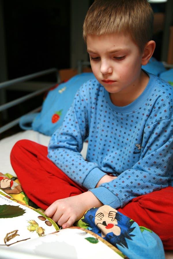 O menino é livro de leitura. fotos de stock royalty free