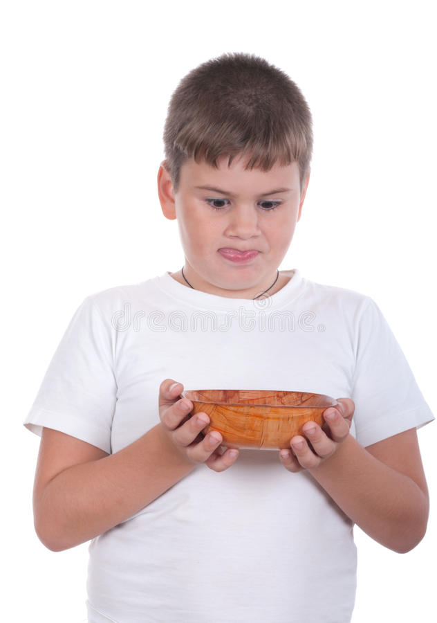 O menino é olhares apetitosos em uma placa fotografia de stock