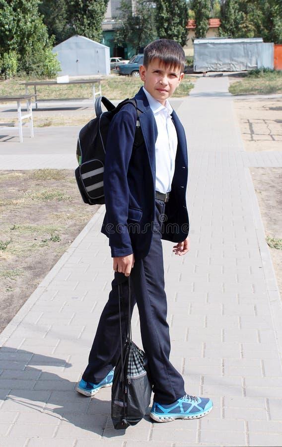 O menino é um aluno em um campo de jogos do ` s das crianças fotos de stock