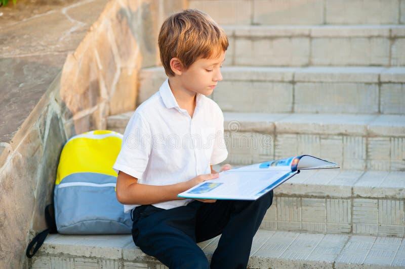 O menino é uma estudante que senta-se nas etapas da escola e que lê um livro Perto de uma trouxa e de um pacote com imagens de stock royalty free