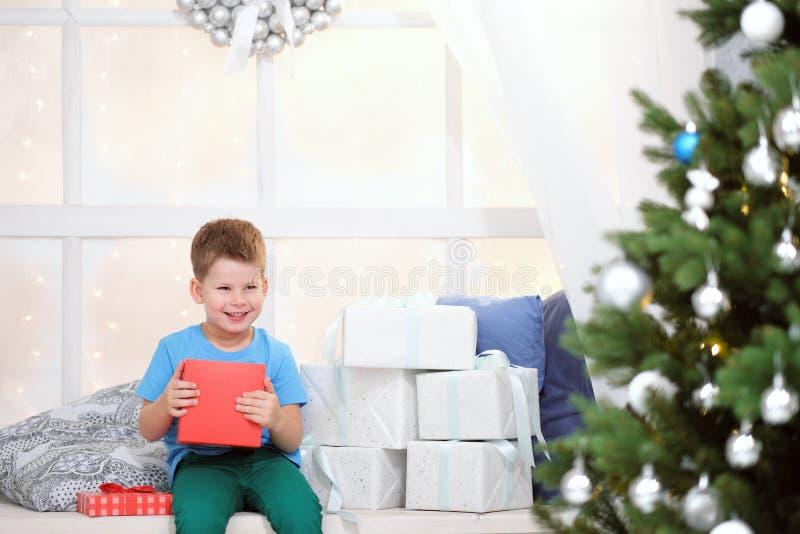 O menino abre uma caixa com um presente de Natal imagens de stock royalty free