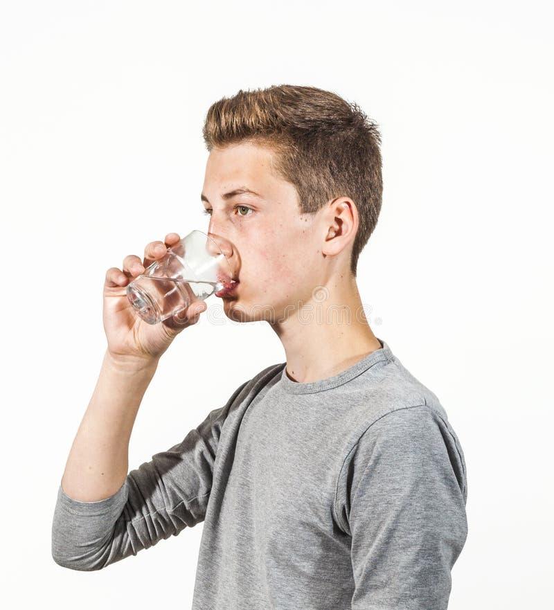 O menino adolescente bebe a água imagens de stock