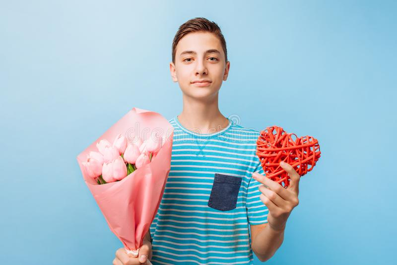 O menino adolescente dá um presente e as flores, um homem no amor, em um fundo azul fotos de stock royalty free
