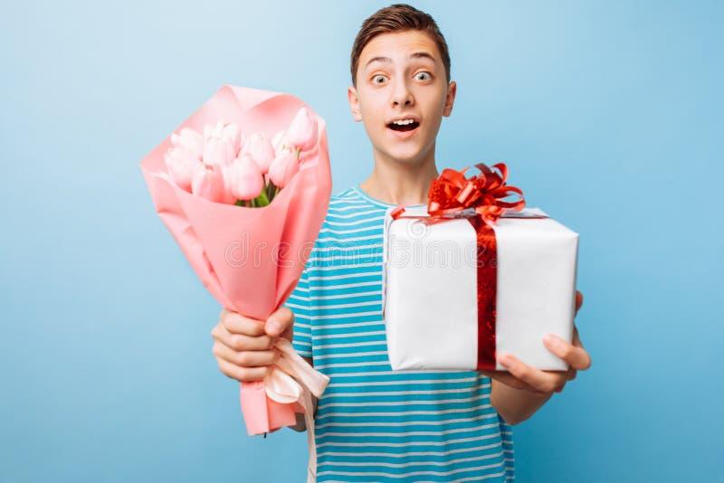 O menino adolescente dá um presente e as flores, um homem no amor, em um fundo azul imagem de stock