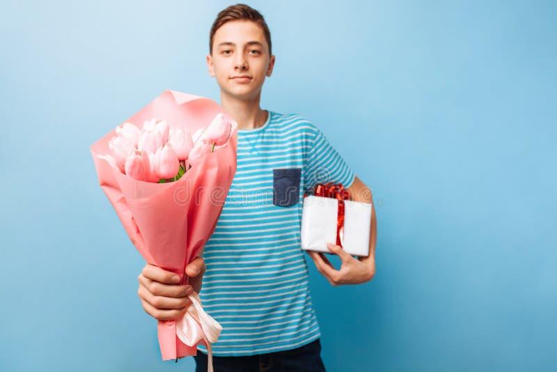O menino adolescente dá um presente e as flores, um homem no amor, em um fundo azul fotos de stock