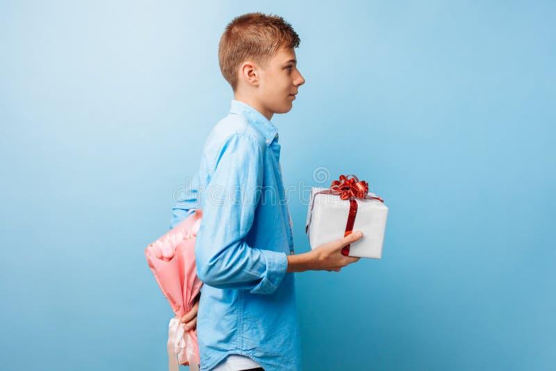 O menino adolescente dá um presente e as flores, um homem no amor, em um fundo azul foto de stock royalty free