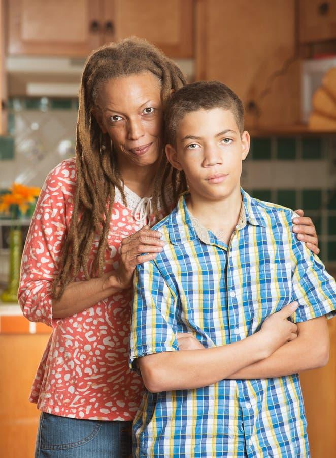 O menino adolescente desagradável está fazendo caretas ao lado de sua mãe loving fotografia de stock