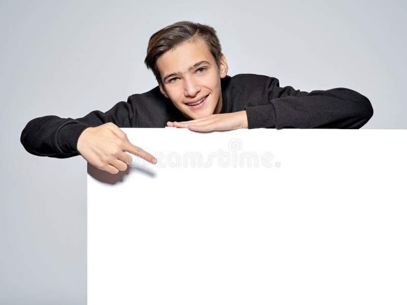 O menino adolescente está apontando pelo dedo para esvaziar a bandeira branca foto de stock