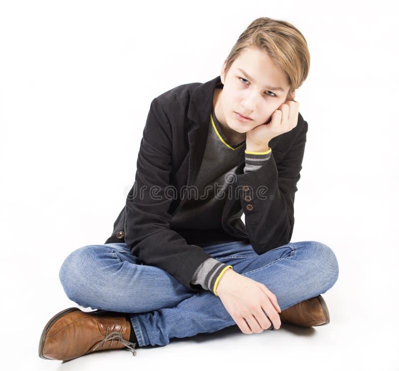 O menino adolescente triste caucasiano de sorriso senta-se na farinha fotos de stock