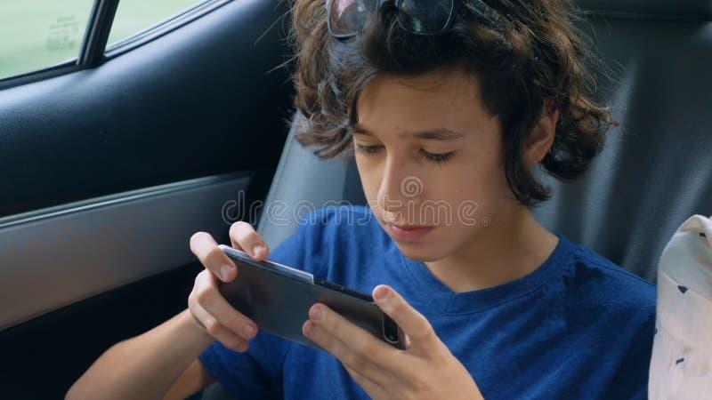 O menino adolescente usa o telefone ao viajar no carro imagens de stock
