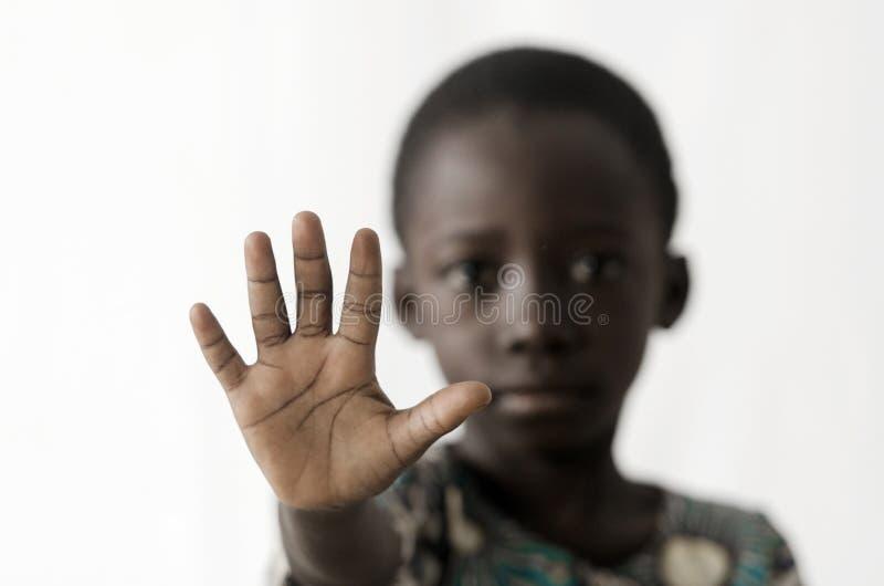 O menino africano faz um sinal da PARADA com sua mão, isolada no branco fotografia de stock