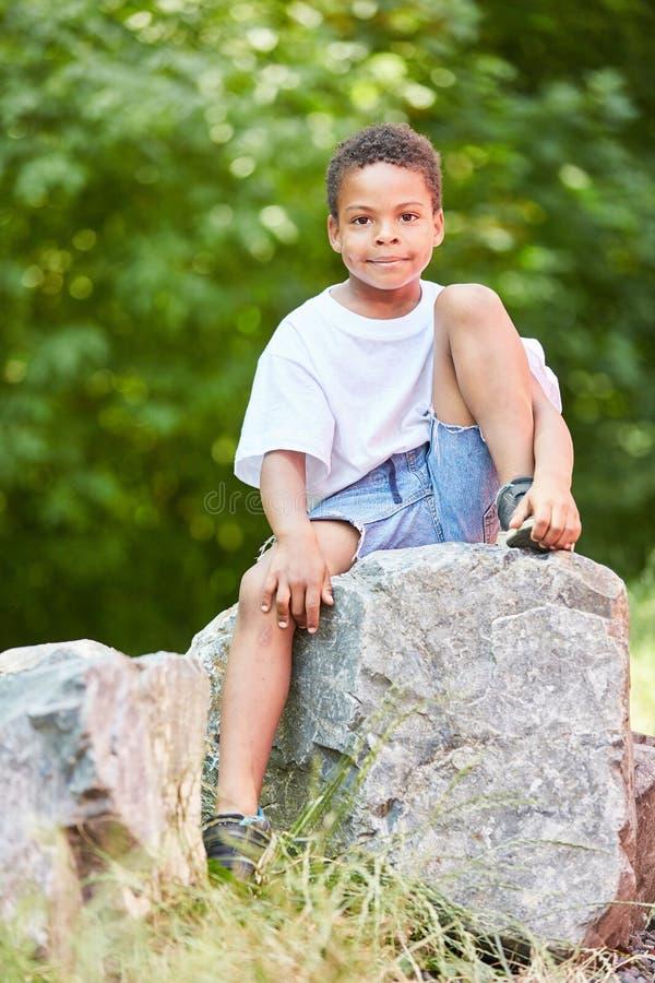 O menino africano senta relaxado em uma pedra fotos de stock royalty free