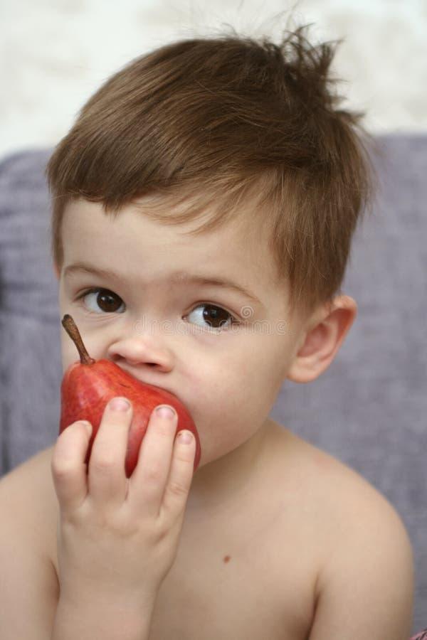 O menino agradável come uma pera vermelha fotografia de stock royalty free
