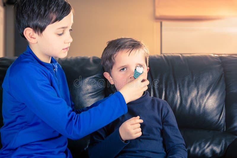 O menino ajuda o irmão com inalador da asma imagem de stock royalty free