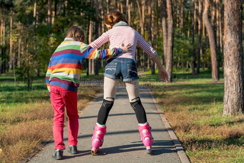 O menino ajuda a menina a patinar no parque Irmão supl. imagem de stock