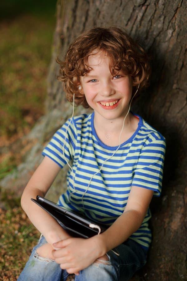 O menino alegre senta-se sob uma árvore com a tabuleta no regaço e põe-se para fora a língua imagens de stock
