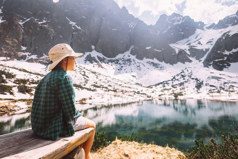O menino aprecia com a luz do sol macia que senta-se no banco de madeira perto do foto de stock royalty free