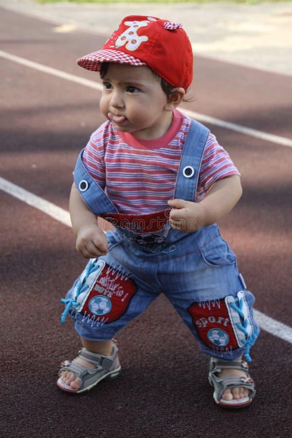 o menino aprende andar e língua das mostras em uma escada rolante imagens de stock royalty free