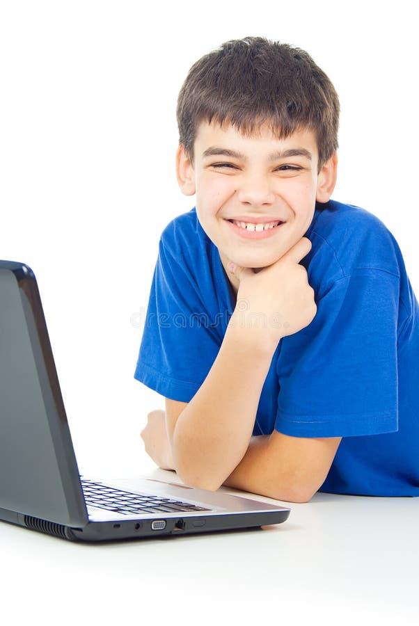 O menino aprende lições em um portátil imagens de stock