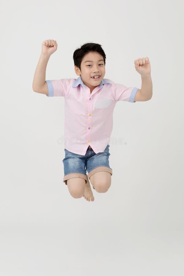 O menino asiático feliz está saltando no estúdio fotografia de stock royalty free