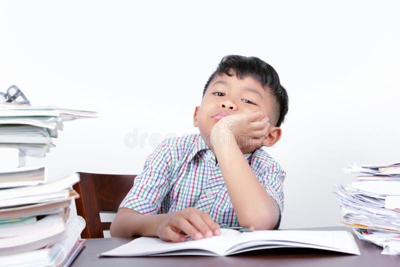 O menino asiático olha o estudo furado em uma mesa e em um fundo branco foto de stock royalty free