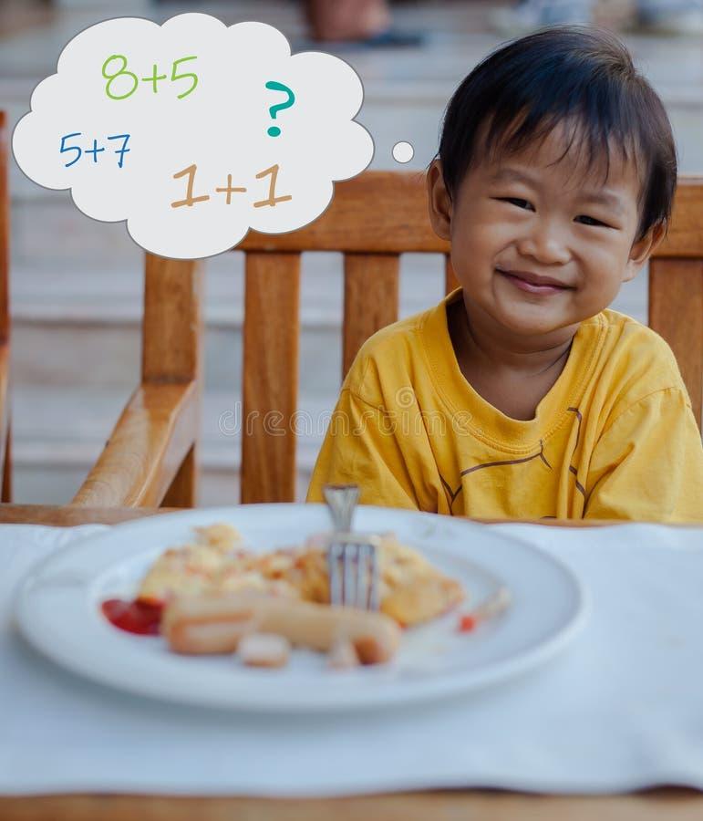 O menino asiático pensa que aproximadamente matemático durante coma o café da manhã imagens de stock