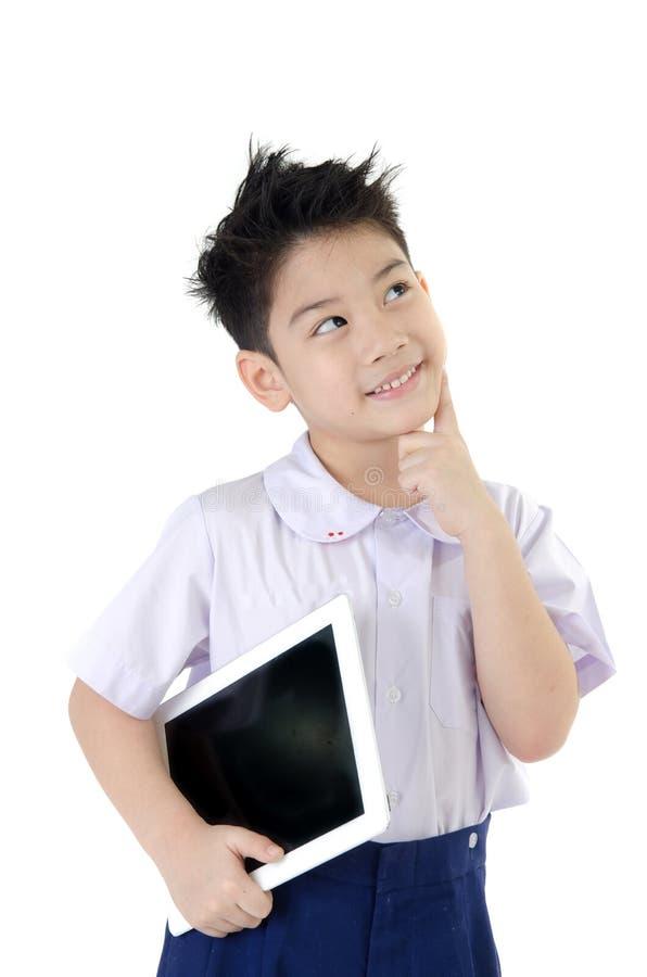 O menino asiático pequeno no uniforme do estudante com tablet pc é sobre foto de stock royalty free