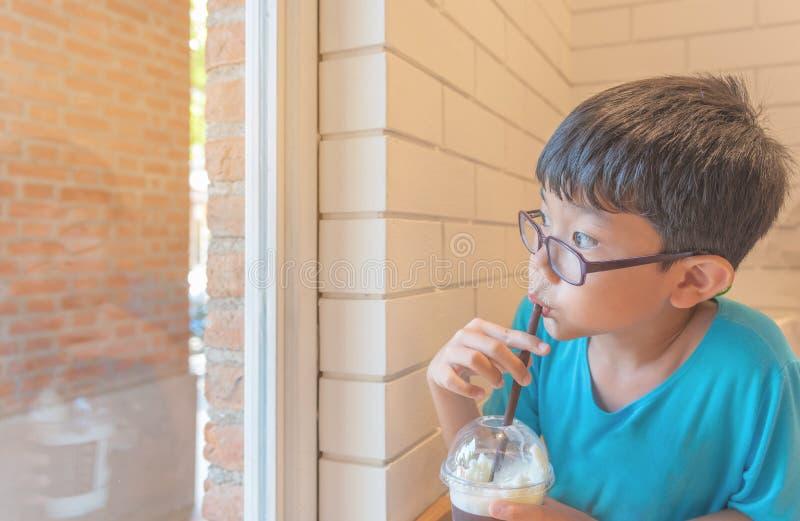 O menino asi?tico suga o leite pela palha pl?stica fotografia de stock royalty free