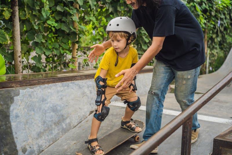 O menino atlético aprende ao skate com um instrutor em um parque do patim Educação das crianças, esportes foto de stock