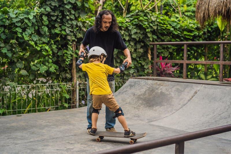 O menino atlético aprende ao skate com um instrutor em um parque do patim Educação das crianças, esportes imagem de stock royalty free