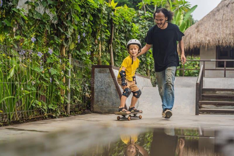 O menino atlético aprende ao skate com um instrutor em um parque do patim Educação das crianças, esportes imagem de stock