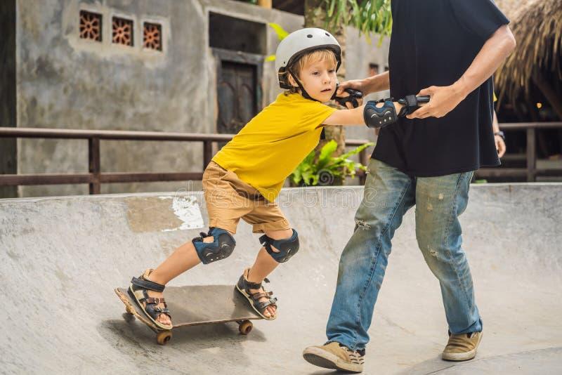 O menino atlético aprende ao skate com um instrutor em um parque do patim Educação das crianças, esportes fotos de stock