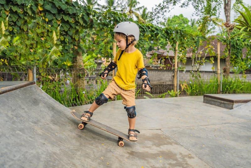 O menino atlético em almofadas do capacete e de joelho aprende ao skate com em um parque do patim Educação das crianças, esportes imagem de stock