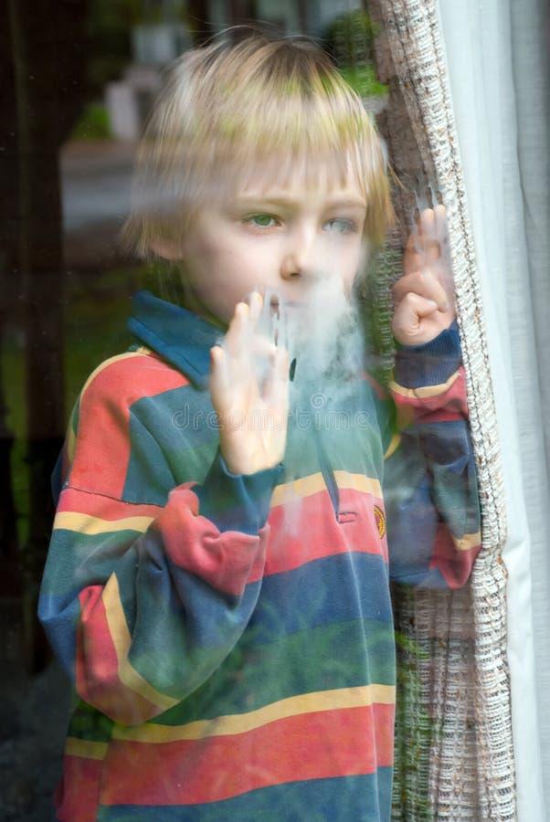 O menino atrás de um indicador molhado imagem de stock