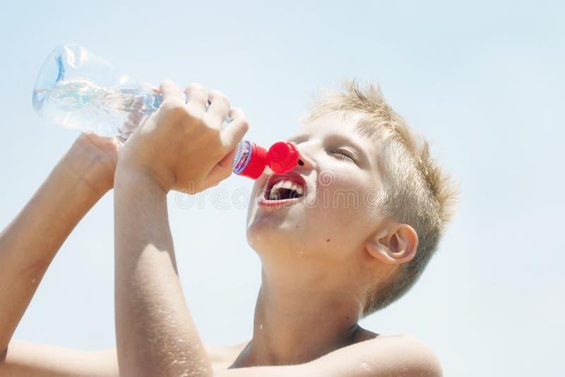 O menino bebe a água de uma garrafa fora fotos de stock royalty free