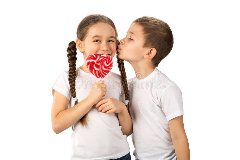 O menino beija a menina com o pirulito vermelho dos doces na forma do coração isolado no branco imagens de stock royalty free